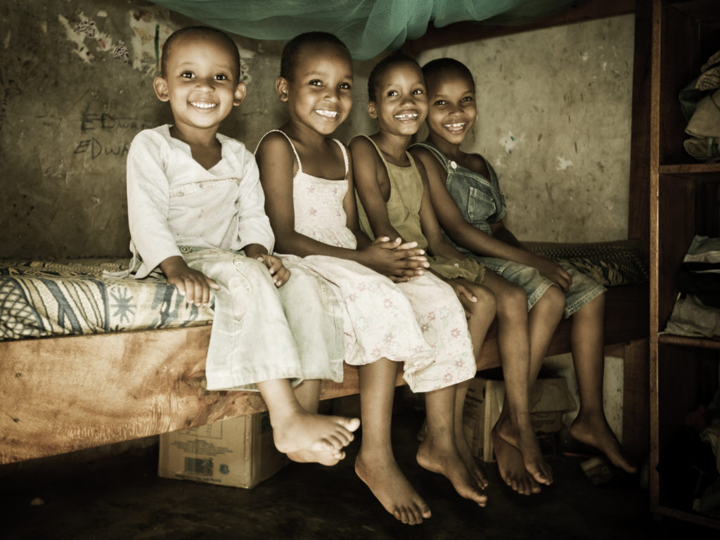 Four young African girls sitting together on a bed in an orphanage. Two girls occupy one bed when they sleep at night.
